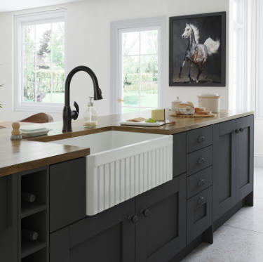 A white and black kitchen with a painting of a horse and a large white fireclay sink