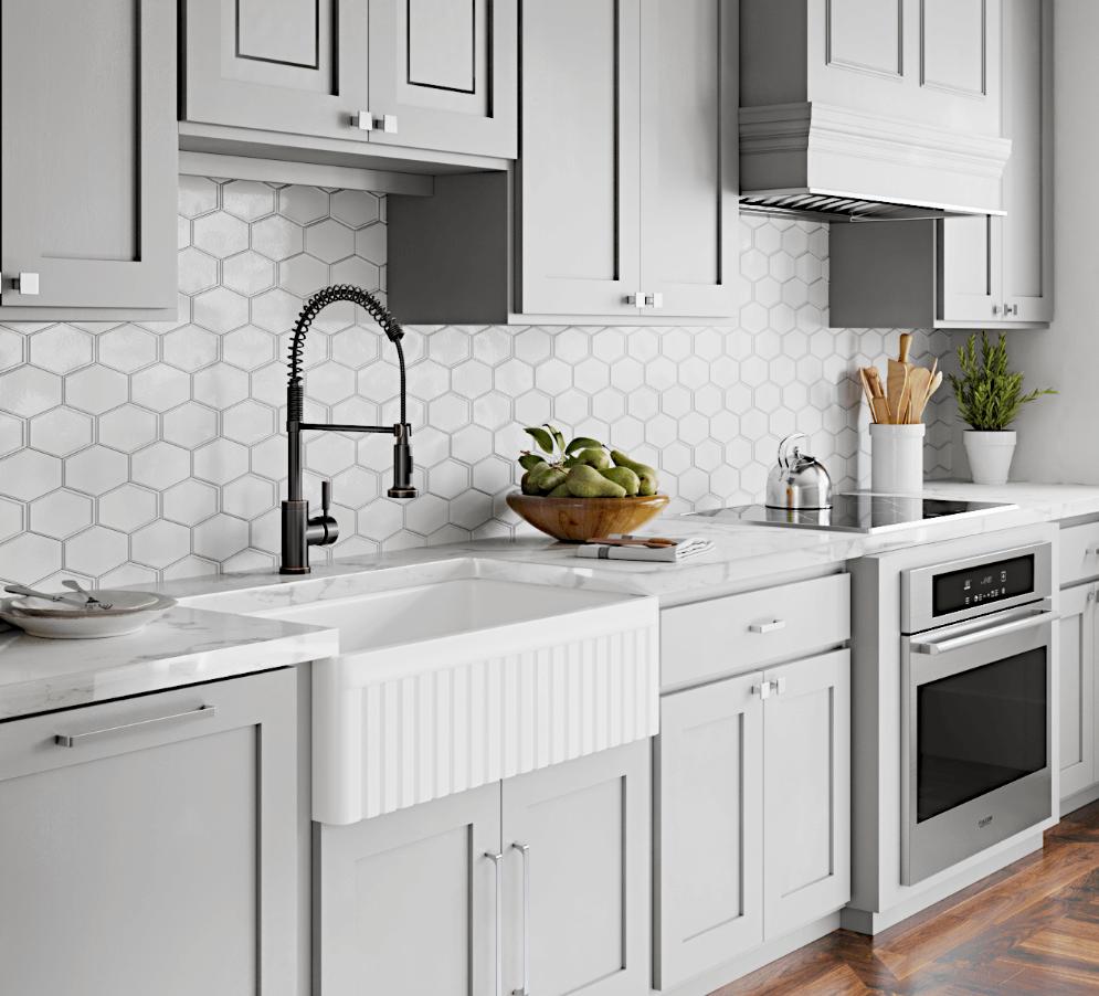 Farmhouse kitchen with a minimalistic hexagon backsplash that gives the fireclay sink a modern twist.