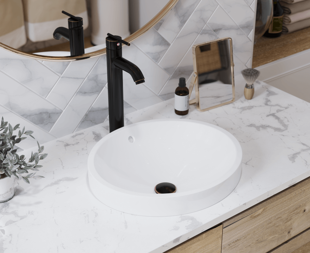 Topmount porcelain bathroom sink on a marble countertop with a hexagon tile wall.