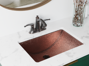 Copper undermount bathroom sink with marble countertop on a green cabinetry.