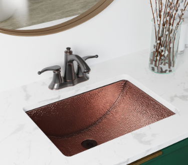Copper bathroom sink with a gold circle mirror and clean white marble countertops.