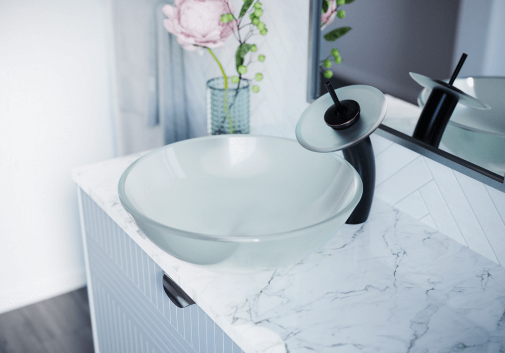 Clean and crisp glass vessel sink with an antique bronze faucet.