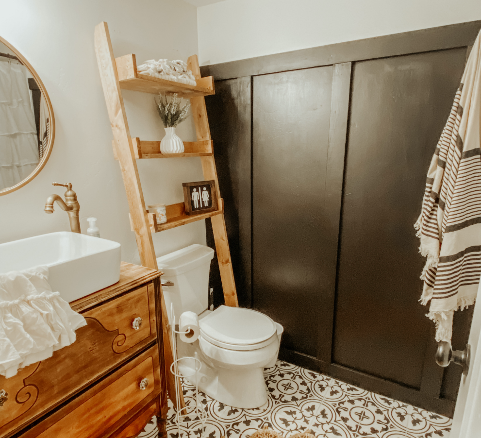 Farmhouse bathroom design with clean and elegant white porcelain sink. Black and white tile  flooring, black board and batten wall, and a wooden angled shelf.