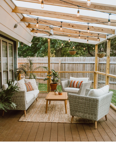 Cozy Boho patio area with wicker furniture, lights, and greenery.