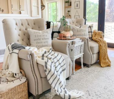 Spacious farmhouse seating area with accent blankets and pillows, seasonal pillows, and fall decor elements.