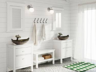 Bright white vanity and mirrors with rustic shiplap wall and accent glass vessel sinks inside of a bright bathroom with plenty of natural light.