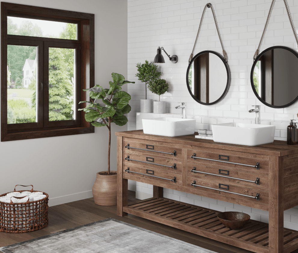 Rustic antique vanity inside of farmhouse bathroom with white porcelain vessel sinks, subway tile backsplash and greenery accents.