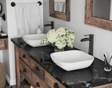 Rustic antique vanity cabinetry with white stone composite sinks and black marble countertop inside of the farmhouse bathroom.