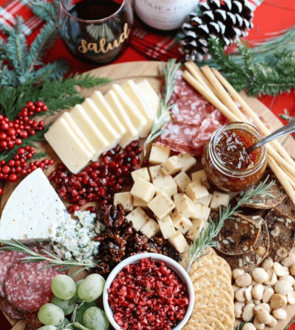 Holiday charcuterie and drinks set out on a decorative cutting board.