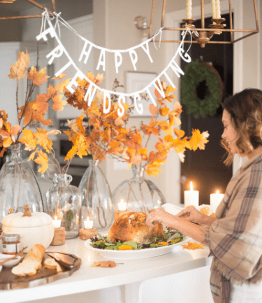 The holiday dinner party scene is set with festive candles and music.