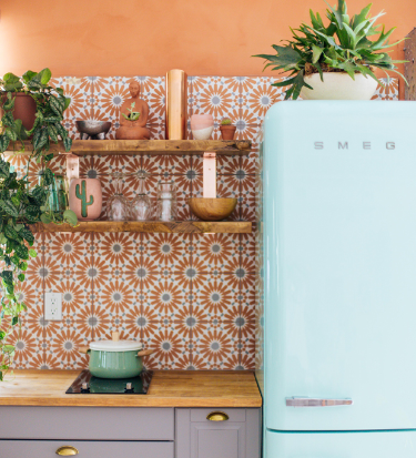 Bright and airy bohemian kitchen with vibrant moroccan tile, baby blue vintage refrigerator with natural light and plants.