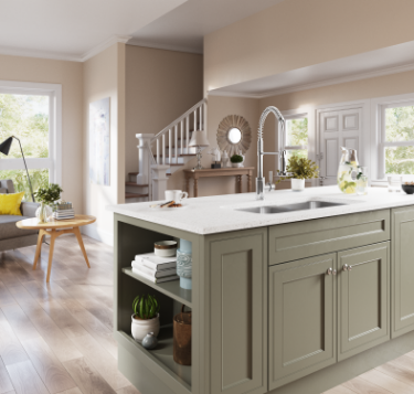 Bright & airy kitchen design with dark green island and large stainless steel sink.