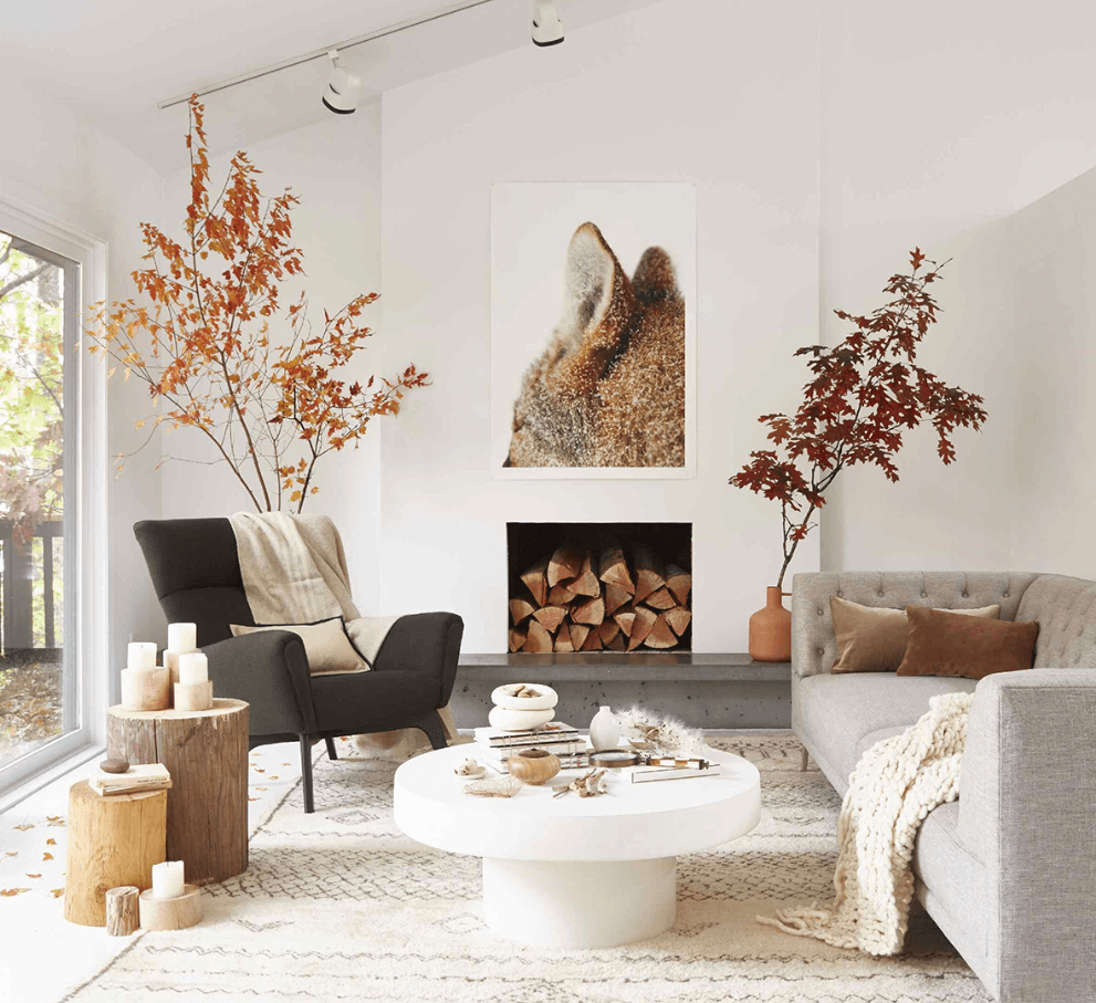 Spacious Scandinavian living room with cozy accent blankets and pillows, wooden side tables, and a minimalistic fireplace with wood burning.