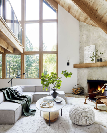 Rustic concrete fireplace, floor to wall windows, and cozy blankets side of a warm Scandinavian living room.