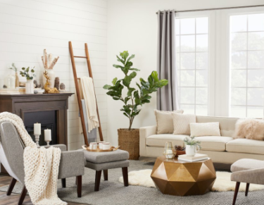 Minimalistic Scandinavian living room with a rustic shiplap accent wall and cozy furniture with knitted blankets.