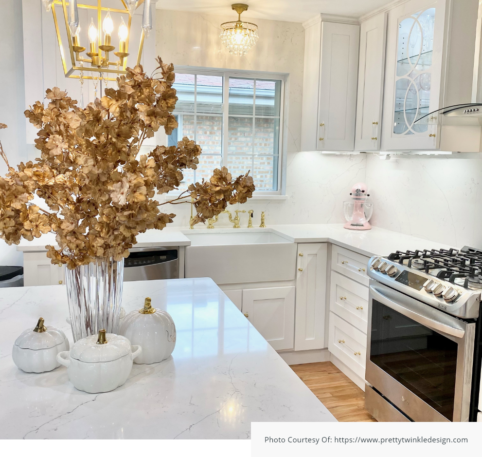 White modern kitchen design with single bowl fireclay farmhouse sink, gold faucets and fall decorations with white cabinets.