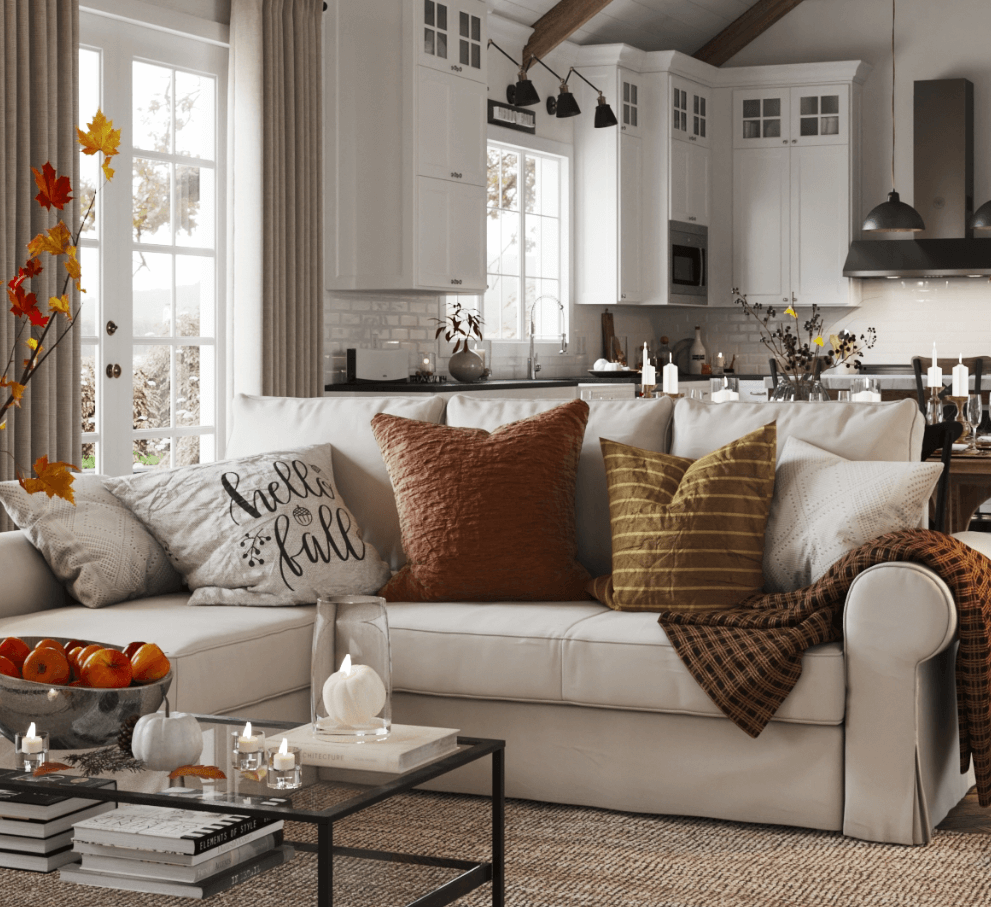 Spacious and neutral-colored living room with fall colored accent pillows, pumpkins, and cozy blankets.