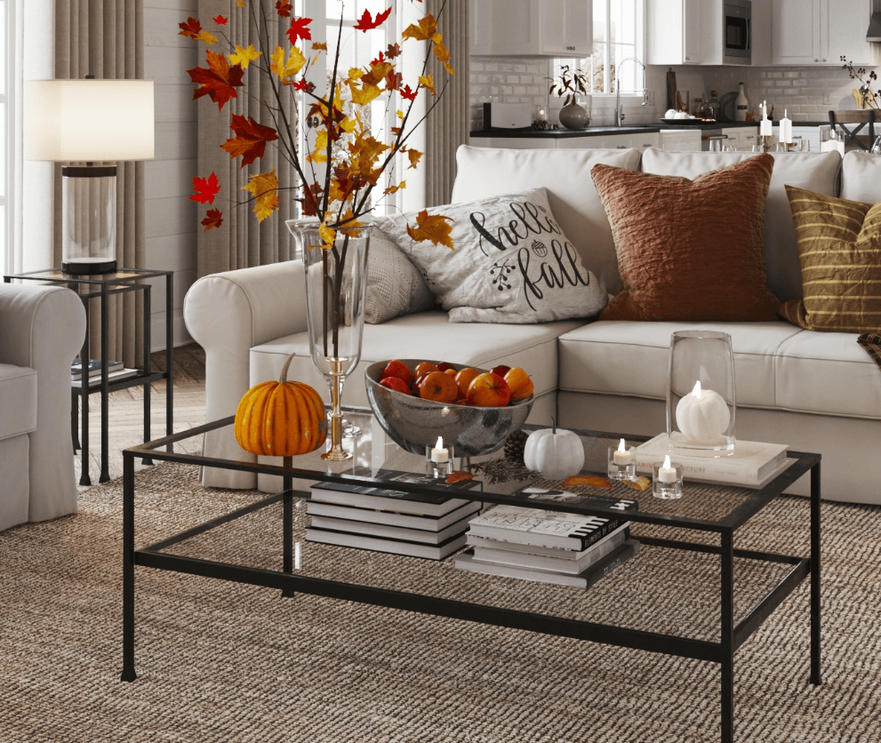 Fall leaves, candles, and pumpkins on an industrial coffee table.