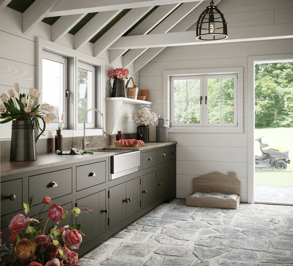 Stainless steel farmhouse sink inside of shabby chic she shed with natural rock flooring, freshly picked flowers and white wooden beams.