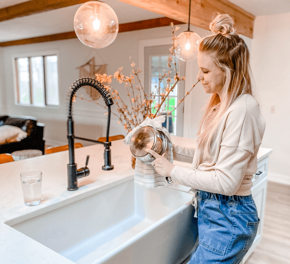 Kait Entsminger from Loved By Kait with an MR Direct apron farmhouse fireclay sink and an antique bronze spring-spout industrial style faucet