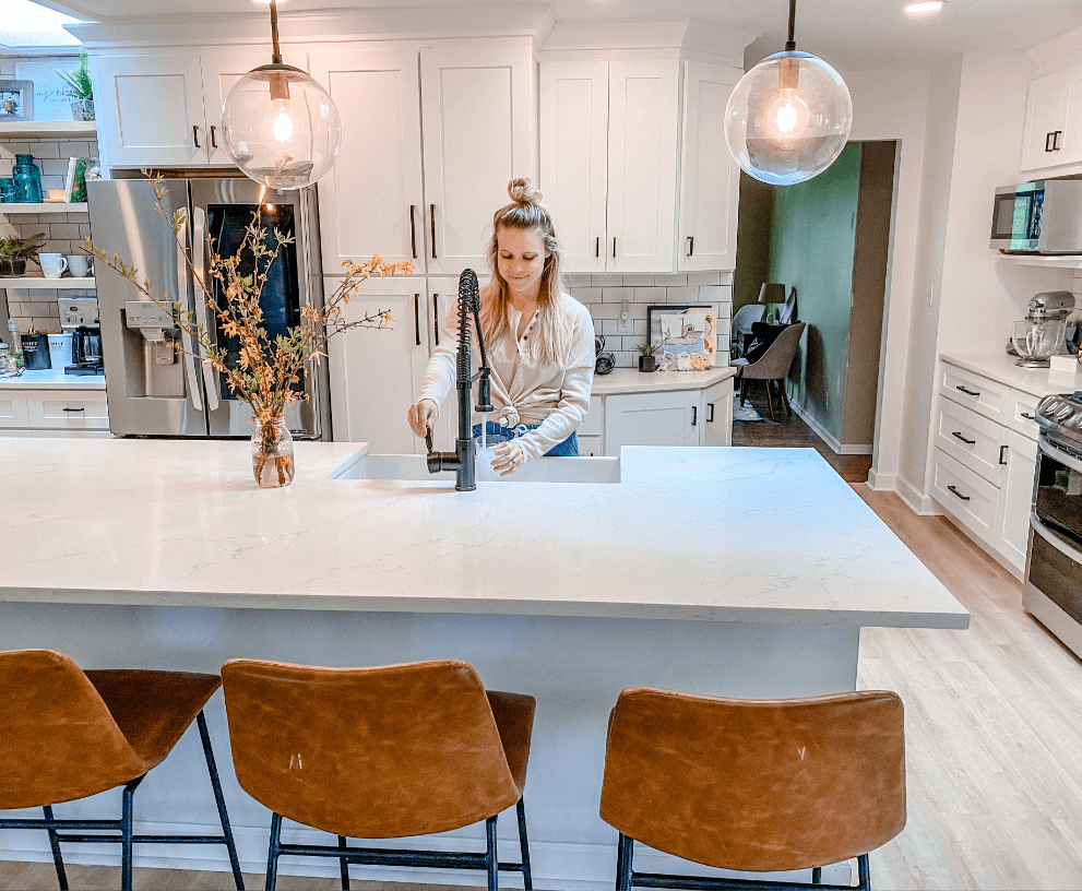 Finished kitchen remodel with crisp white cabinets, matte black knobs, bar seating, black pendant lighting over a kitchen island, an farmhouse fireclay sink and an antique bronze faucet.
