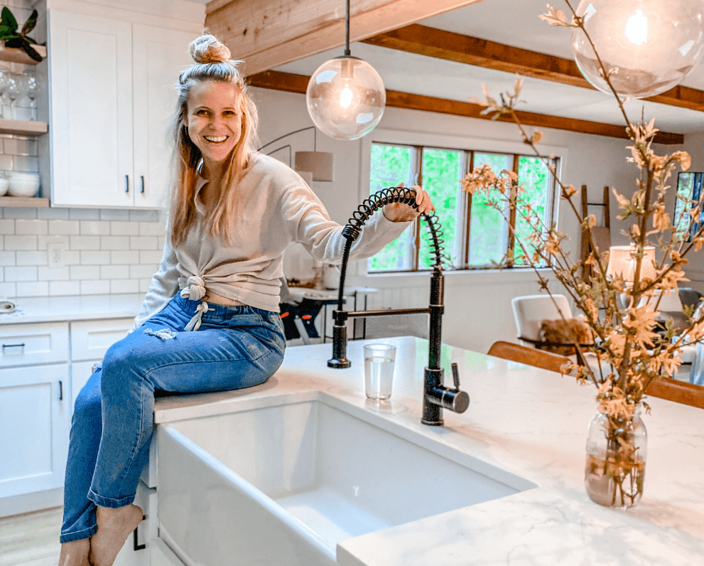 Kait Entsminger from Loved By Kait inside of a farmhouse modern kitchen with an MR Direct apron fireclay sink and antique bronze faucet..