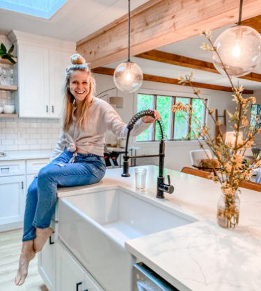 Kait Entsminger from Loved By Kait inside of a farmhouse modern kitchen with an MR Direct apron fireclay sink and antique bronze faucet.