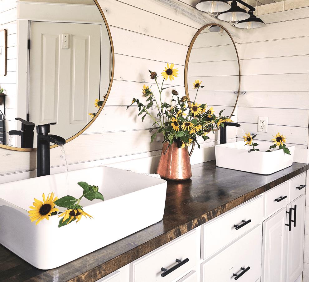 Modern farmhouse bathroom design with white porcelain vessel sinks, crisp white cabinets, rustic butcher block countertops, and matte black accents.