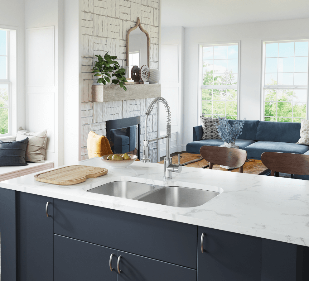 Farmhouse home design with navy blue cabinets on a marble island with a stainless steel sink and antique brick fireplace.