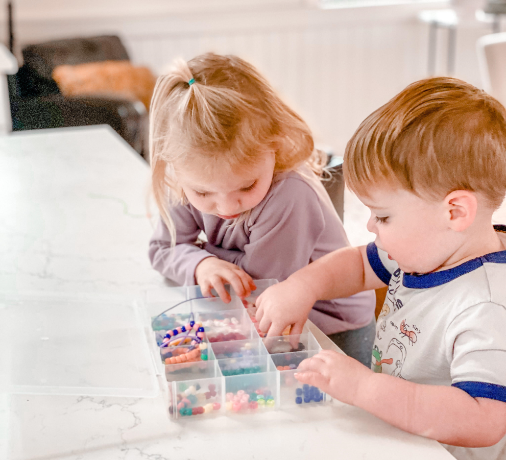 A young girl and a young boy looking through beads in a plastic organizer