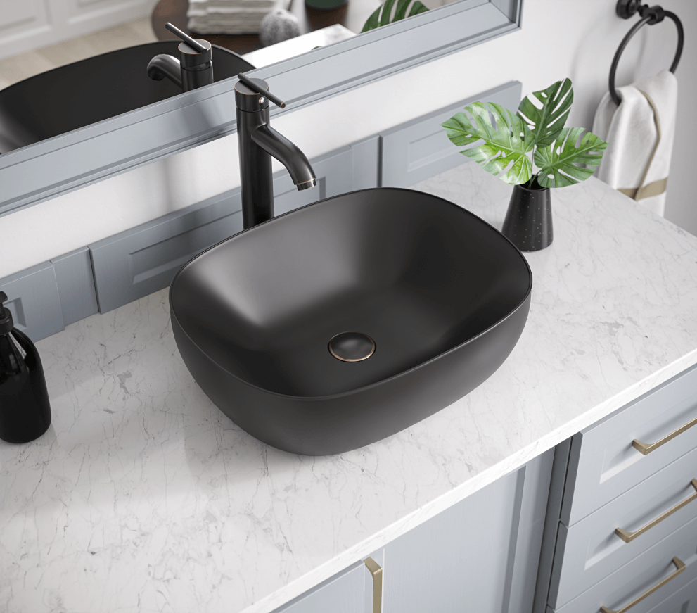 Matte black porcelain vessel sink on marble countertop and light blue vanity.
