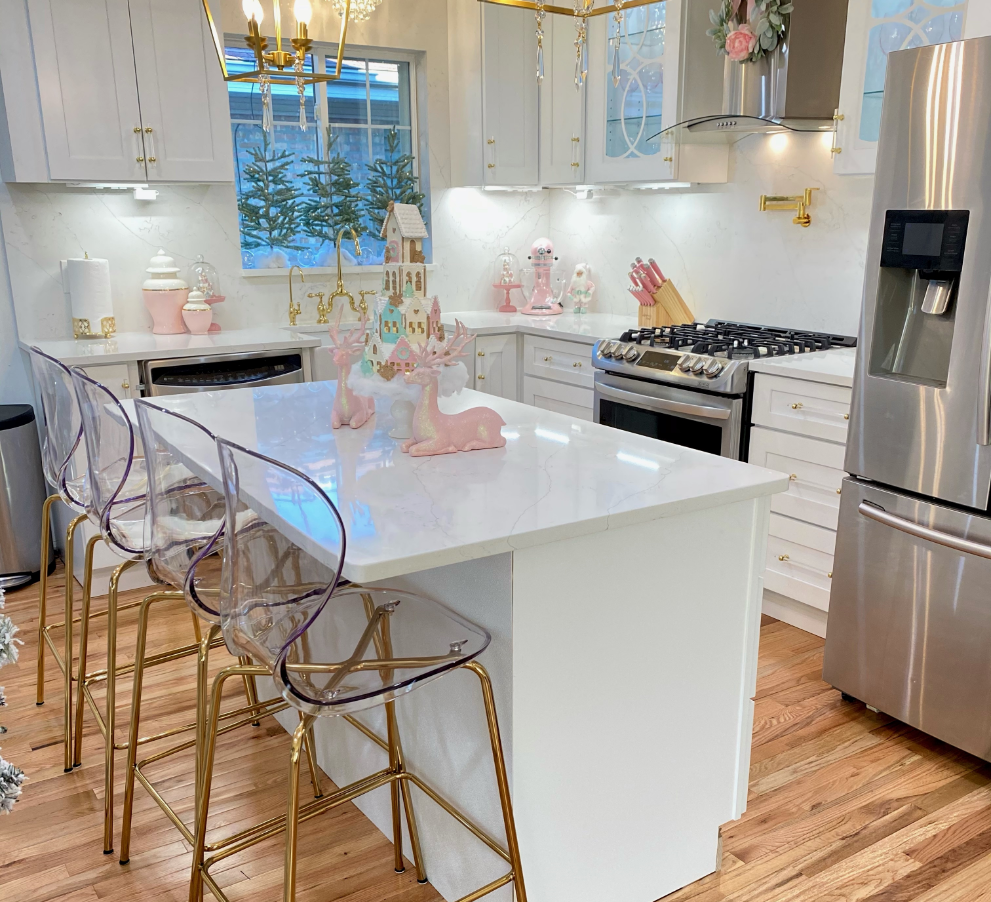 White and gold modern kitchen with stainless steel appliances and christmas decorations