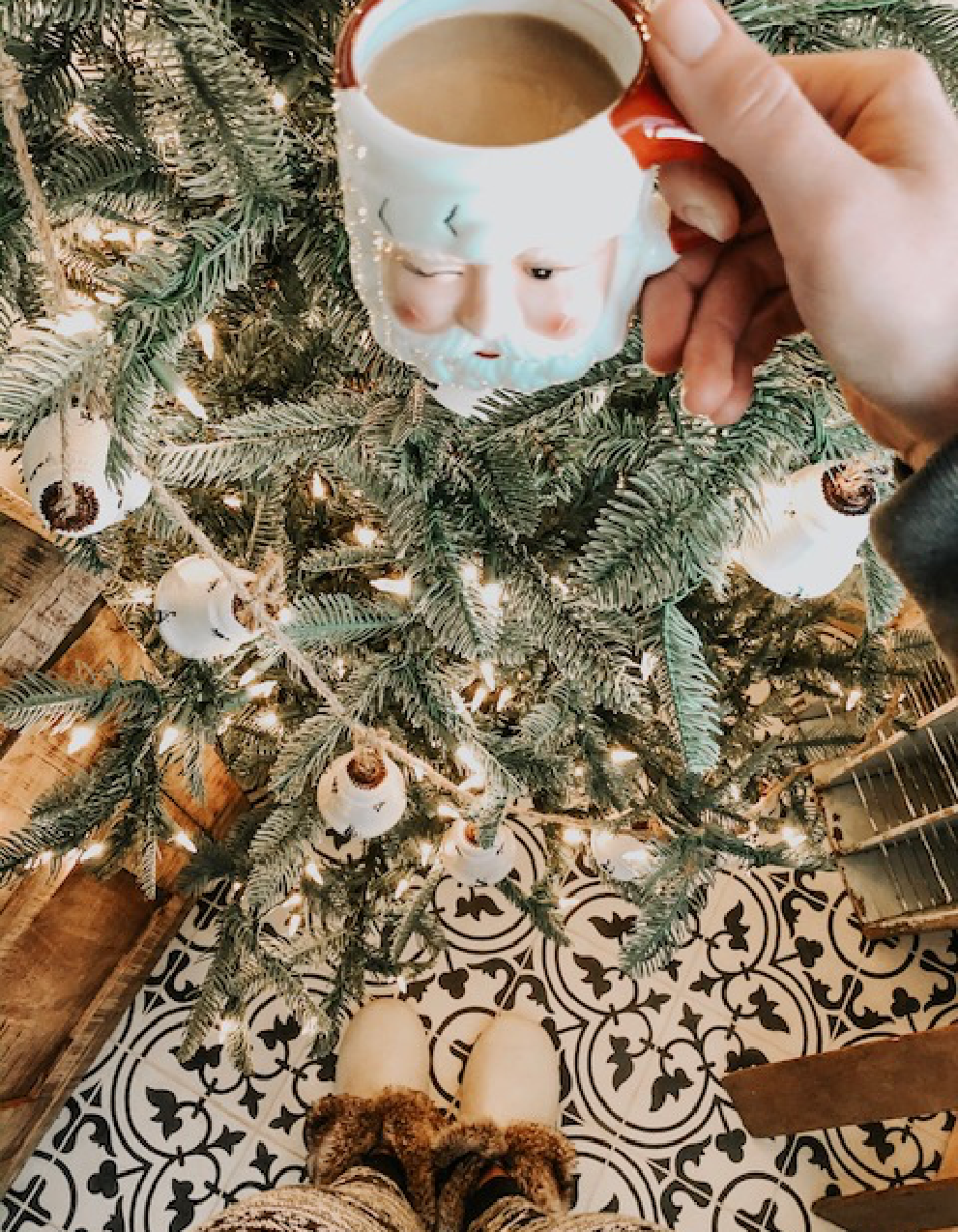 Santa Claus mug filled with coffee in front of a beautifully decorated Christmas tree.