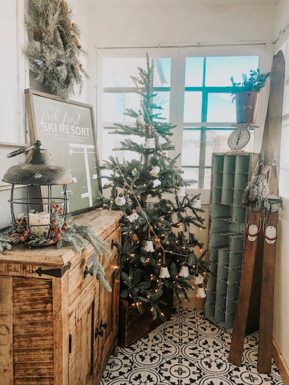 Sun porch decorated with a faux Douglas fir Christmas tree and a pair of 1940 wooden skis!