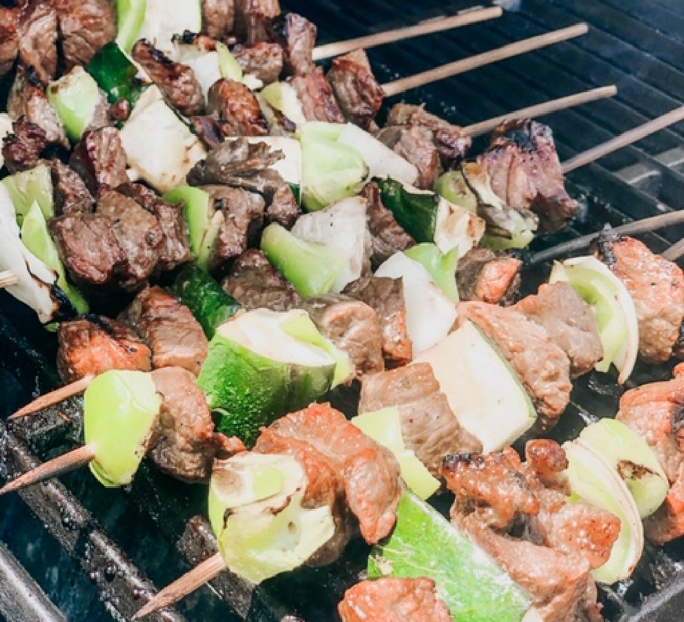 Fresh zucchini, green peppers and onions and marinated beef kabobs being grilled for a summer BBQ!