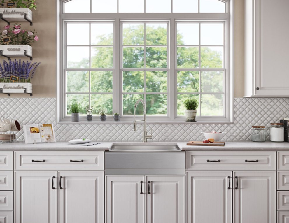 Deep stainless steel apron sink inside of farmhouse kitchen design with open flower planters and large windows.