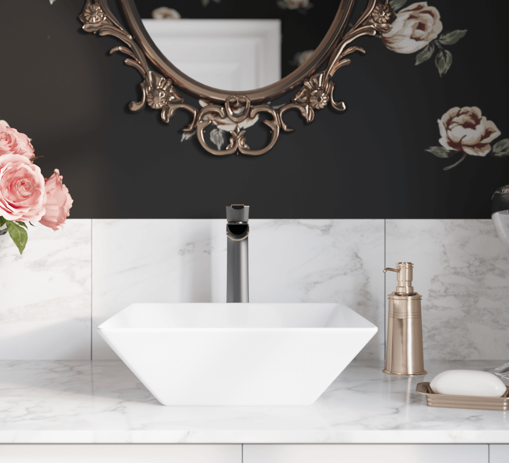 Vessel porcelain sink inside of a glam room with floral wallpaper and gold mirror.