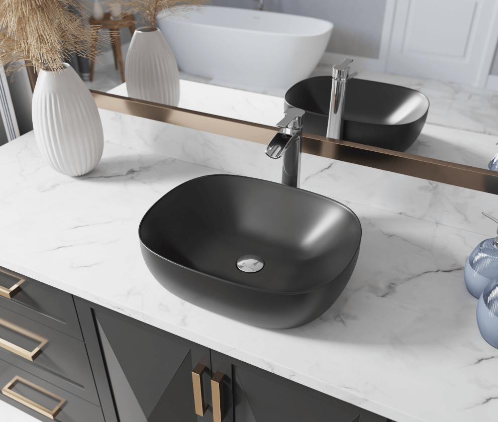 Matte black porcelain sink on a marble countertop with gold finishes.