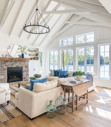 Bright and airy lake cottage with large windows for a scenic view and sky blue accents for a coastal vibe.