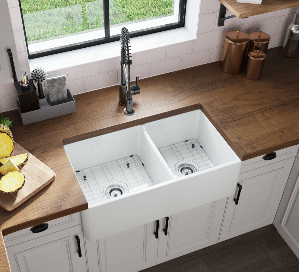 Fireclay farmhouse sink with butcher block countertops and crisp while cabinetry.