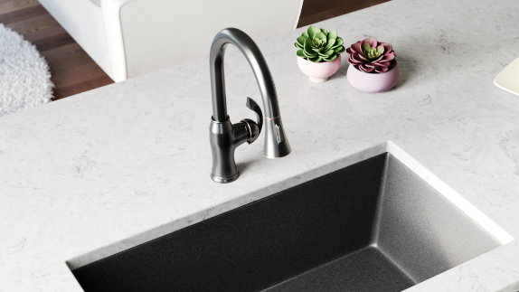 Dark faucet on a white countertop with a black granite sink